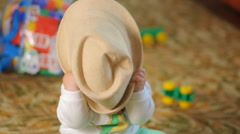 Beautiful baby trying to eat his hat. The boy is less than a year - stock footage