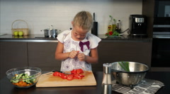 Little girl preparing salad in the kitchen Stock Footage