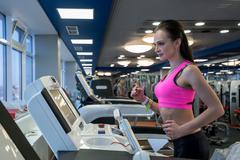 Shot of focused girl running on treadmill in gym Stock Photos