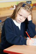 Bored Female Elementary School Pupil At Desk Stock Photos