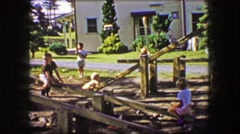 1944: Kids play wood see saw teeter totter only outdoor playground. Stock Footage