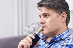 Mature Man Using Vapourizer As Smoking Alternative Stock Photos
