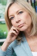 Head And Shoulders Portrait Of Thoughtful Mature Woman At Home Stock Photos