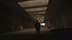 An industrial worker walks through a dark tunnel - stock footage