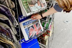 Woman buying Le Figaro newspaper with shocking headline about Brexit - stock photo