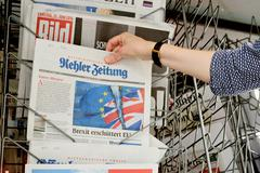 Woman buying Kehler Zeitung newspaper with shocking headline about Brexit - stock photo