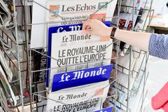 Woman buying Le Monde newspaper with shocking headline about Brexit Stock Photos