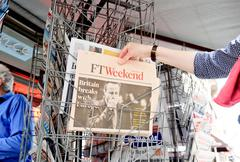 Woman buying Financial Times newspaper with shocking headline about Brexit - stock photo