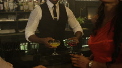 4K Barman serving drinks to happy young party crowd in trendy city bar - stock footage