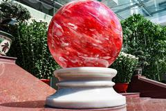 Glass red ball on a pedestal Stock Photos