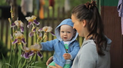 Little kid touches a flower on my mother's hands. The boy is less than a year - stock footage