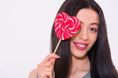 Pleasant smiling woman holding lollypop Stock Photos