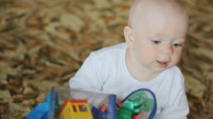 Baby playing at home on the floor with toys. Handsome boy less than a year Stock Footage