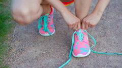 Hands of a young woman lacing bright pink and blue sneakers. Running shoes - Stock Footage