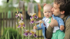 Mother touching baby with a flower after a rain. Handsome boy less than a year - stock footage