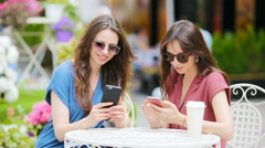 Two young girls using smart phone at the outdoors cafe. Two women after shopping - stock footage