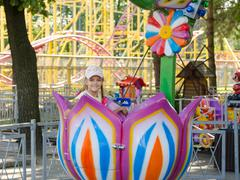 Six-year girl riding on a carousel, sitting in a stylized floret - stock photo