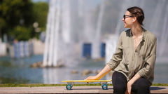 Young girl having fun with skateboard in the park. Lifestyle portrait of young Stock Footage