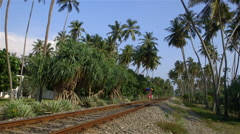 WOMAN WALKS ON RAILWAY LINE BENTOTA SRI LANKA Stock Footage