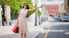 Young happy girl with shopping bags catch a taxi. Portrait of a beautiful happy - stock footage