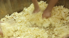 Many hands crushed cheese in a wooden bucket Stock Footage