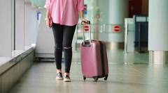 Closeup airplane passenger with passports and boarding pass and pink baggage in Stock Footage