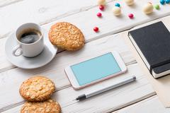 White smart phone on a desktop. Clipping path included Stock Photos