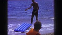 1955: Dad trying to convince toddler son to come swimming at ocean beach. Stock Footage