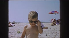 1955: Cool toddler kid wearing Ray Ban wayfarer style sunglasses on white sands Stock Footage