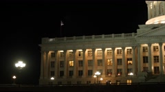 Flag flies at the Utah State Capitol at night panning shot Stock Footage