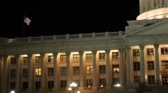 Flag flies over the Utah State Capitol at night Stock Footage