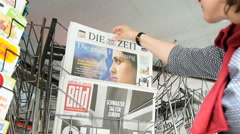 Woman buying Bild Germany newspaper with shocking headline about Brexit Stock Footage