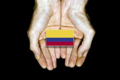 Flag of Colombia in hands on black background - stock illustration