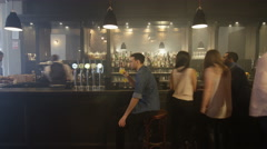 4K Timelapse of man sitting at a busy bar while young crowd socialize around him Stock Footage