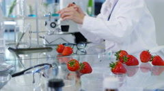 4K Food science researchers working in lab, woman injecting chemicals into fruit Stock Footage