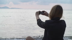Woman use smatphone on beach at sunset Stock Footage