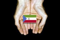 Flag of Equatorial Guinea in hands on black background - stock illustration