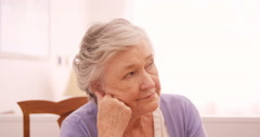 Thoughtful senior woman sitting at home Stock Footage