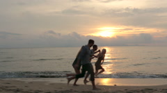 Couples run and have fun on beach at sunset Stock Footage