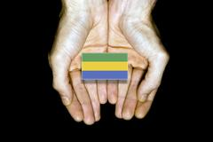 Flag of Gabon in hands on black background - stock illustration