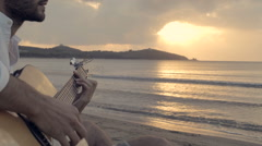 Young beautiful man seated outdoor on shore play guitar Stock Footage