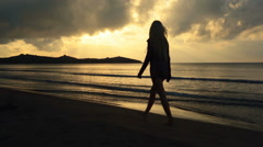 Young beautiful blonde woman silhouette walk on shore at sunset Stock Footage