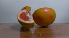 Grapefruit falling in slow motion onto a cutting board and splitting apart Stock Footage