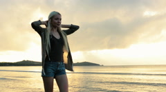 Young beautiful blonde woman walk on shore at sunset in summer Stock Footage