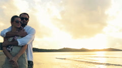 Young romantic boyfrined hug his girlfriend at sunset on shore Stock Footage