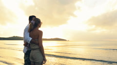 Young romantic embraced couple enjoy sunset on shore in summer Stock Footage