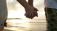 Young romantic couple hold hands at sunset on shore in summer outdoor Stock Footage