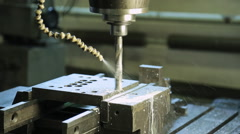 A running CNC machine with a rotating drill and a pipe for cutting fluid Stock Footage
