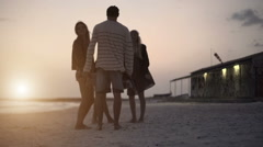 Group of four friends hug and walk away on ocean beach seaside Stock Footage