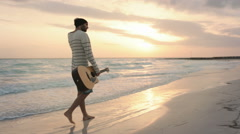Front view of young beautiful man walk along on ocean beach seaside Stock Footage